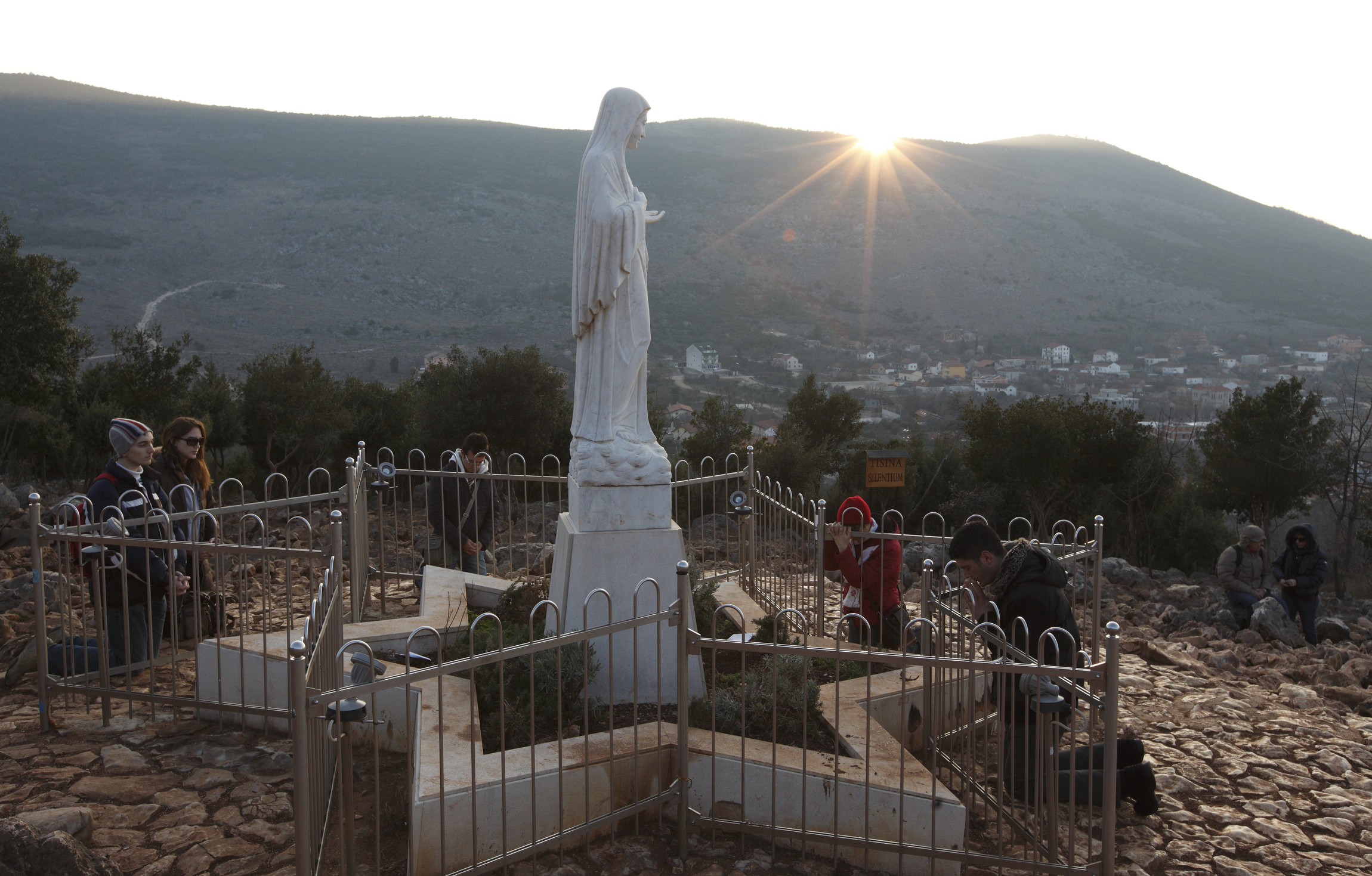 Pilgrims pray around a statue of Mary on Apparition Hill in Medjugorje, Bosnia-Herzegovina, Feb. 26. The site is where six village children first claimed to see Mary in June 1981. A Vatican-appointed commission is studying the alleged Marian apparitions at Medjugorje. CNS photo/Paul Haring) (Feb. 28, 2011) See MEDJUGORJE-PILGRIMS Feb. 28, 2011.